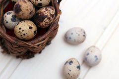 Quail eggs in a wicker basket on a wooden background Royalty Free Stock Photos