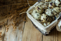Quail eggs in wire basket with dry beige flowers on barn wood, Easter, farming Stock Images