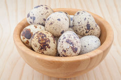 Quail eggs in wooden bowl. On wooden background Royalty Free Stock Images