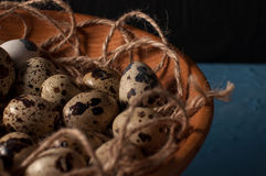 Quail eggs in wooden bowl  on blue background close up Royalty Free Stock Photography