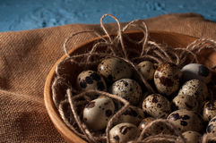 Quail eggs in wooden bowl  on blue background close up Stock Photo