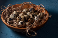 Quail eggs in wooden bowl  on blue background close up Royalty Free Stock Image