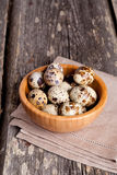 Quail eggs in a wooden bowl on a gray background. Quail eggs  on rustic wooden table, vertical, close up Royalty Free Stock Images