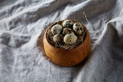 Quail eggs in a wooden bowl on a homespun tablecloth, top view, close-up. Fresh spotted quail eggs in a wooden bowl on a homespun tablecloth, top view, close-up Stock Image