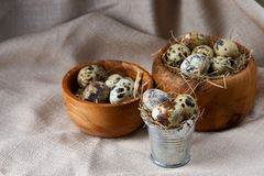 Quail eggs in a wooden bowl on a homespun tablecloth, top view, close-up. Fresh spotted quail eggs in a wooden bowl on a homespun tablecloth, top view, close-up stock photo