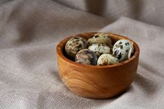 Quail eggs in a wooden bowl on a homespun tablecloth, top view, close-up. Fresh spotted quail eggs in a wooden bowl on a homespun tablecloth, top view, close-up Royalty Free Stock Photography