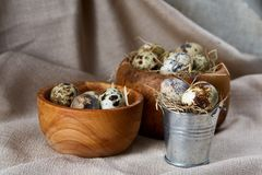 Quail eggs in a wooden bowl on a homespun tablecloth, top view, close-up. Fresh spotted quail eggs in a wooden bowl on a homespun tablecloth, top view, close-up stock photography