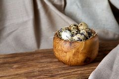 Quail eggs in a wooden bowl on a homespun tablecloth, top view, close-up. Fresh spotted quail eggs in a wooden bowl on a homespun tablecloth, top view, close-up royalty free stock photo