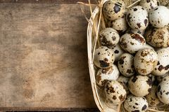 Quail eggs in wooden bowl isolated on wooden background. Healthy food. Quail eggs in a nest on a rustic wooden background. Healthy food concept Stock Photo