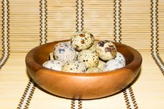 Quail eggs in a wooden bowl on a napkin from natural bamboo. Stock Photo