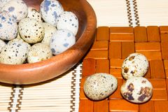 Quail eggs in a wooden bowl on a napkin from natural bamboo. Stock Images