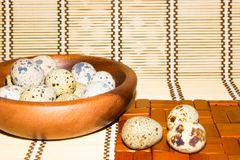 Quail eggs in a wooden bowl on a napkin from natural bamboo. Royalty Free Stock Images