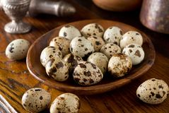 Quail Eggs in a Wooden Bowl. On a rustic table top setting Royalty Free Stock Photos