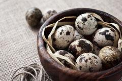 Quail eggs in wooden bowl on sack background. Many quail eggs in wooden bowl on sack background. Close-up Royalty Free Stock Image
