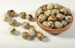 Quail eggs in a wooden bowl in a sacking. Background Stock Images