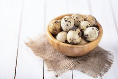 Quail eggs in wooden plate over white background. Raw fresh quail eggs in a bowl on white wooden background, selective focus, copy space stock photos