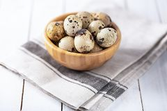 Quail eggs in wooden plate over white background. Raw fresh quail eggs in a bowl on white wooden background, selective focus, copy space stock photography