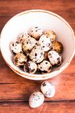 Quail eggs on a wooden vintage table, selective focus. Healthy and organic food option. Easter food. stock photography