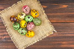 Quail multi-colored Easter eggs on a brown wooden table. Quail multi-colored Easter eggs on a brown wooden table Stock Photos