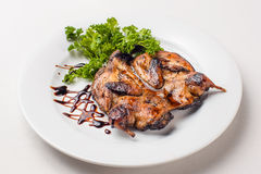 Quail roasted in a dish. On a white background Royalty Free Stock Photography