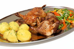 Quails. Fried quails with potatoes and vegetables Royalty Free Stock Images