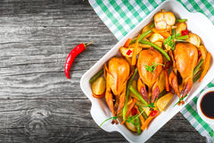 Quails baked with vegetables, top view, close-up Royalty Free Stock Photos