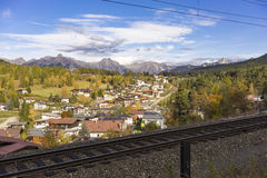 Quaint Alpine Village with Train Tracks. Overview of Quaint Alpine Village with Surrounding Forest and Mountain Range in Background and Train Tracks in Royalty Free Stock Photo