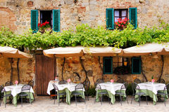 Quaint cafe. Cafe tables and chairs outside a quaint stone building in Tuscany, Italy Royalty Free Stock Image