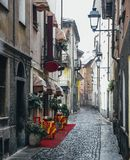 Quaint cobblestone alleyway in Aosta Italy with inviting red carpet entrance to Italian restaurant on left. Quaint cobblestone alleyway in Aosta, Italy with Stock Photo