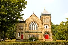 Quaint country church. A view of the front of a small, quaint little Catholic (Christian) stone church with bright red doors on a country hillside Stock Photos