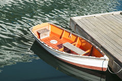 Quaint dinghy alongside pier. Stock Photos