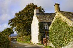 Quaint English country cottage. A view of the side of a quaint English cottage along the side of a narrow country road Stock Photos