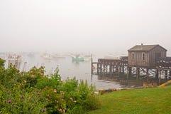 Quaint fishing wharf in fog. A view of a fishing wharf and shack on Bass Harbor in dense, coastal Maine fog Royalty Free Stock Photos