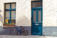 Quaint home with blue door and blue window matching blue bicycle Royalty Free Stock Photo