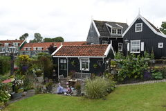 Quaint houses are seen in the Dutch town of Marken. Typical rustic houses with beautiful flower gardens and red tile roofs in the Dutch village of Marken Stock Images