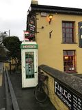 Quaint Irish Scene of Telephone Booth and Bicycle. An Irish telephone booth, bicycle and Gaelic signs in quaint village Stock Images