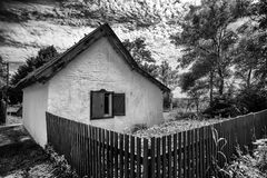 Quaint little old abandoned house sitting behind broken wood fence Royalty Free Stock Image