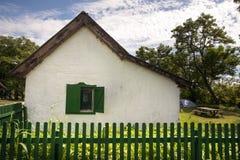 Quaint little old abandoned house sitting behind broken wood fence Stock Image