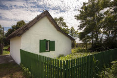 Quaint little old abandoned house sitting behind broken wood fence Royalty Free Stock Photo