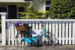 Quaint Living. Quaint Beach Side Living - A beach cottage, white fence, small garden, bicycle in front Royalty Free Stock Photography