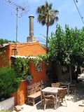 Quaint Mediterranean cafe. Exterior of quaint traditional Mediterranean cafe with outdoor seats and green trees Stock Photos
