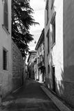 Quaint narrow street with old stone houses. Disappearing into the distance in a greyscale architectural image Royalty Free Stock Image