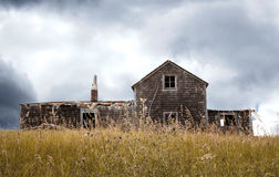 Quaint old abandoned wood house sitting in tall grass Royalty Free Stock Images