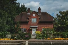 Quaint Old English Home Along the River Thames. A quaint red brick, old English home along the River Thames. The symmetrical home is nearly swallowed by lush stock images