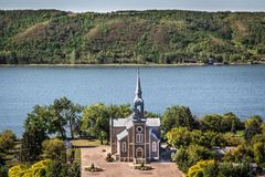 Quaint stone church sitting next to a blue lake. Beautiful quaint stone brick church sitting next to a lake surrounded by green rolling hills in the summer time Royalty Free Stock Images