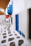 Quaint Street with Blue and Red Doors. Quaint, colorful street in Mykonos, Greece. Vertical royalty free stock image
