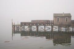 Quaint visserijwerf in mist stock afbeelding