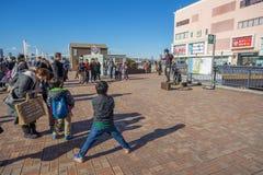 Qualche gente che esegue davanti alla costruzione della città dell'acqua fotografia stock libera da diritti