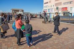 Qualche gente che esegue davanti alla costruzione della città dell'acqua immagine stock