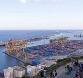Qualche gente prende un resto alla collina Montjuic con una visualizzazione alla parte industriale del porto di Barcellona Immagine Stock